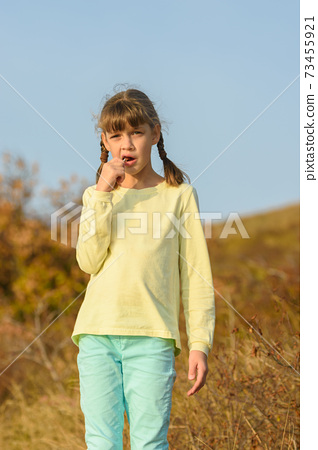 The girl nibbles on a lollipop and looks at the frame with a puzzled look 73455921