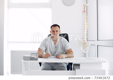 Doctor in a white uniform at the office 73461672