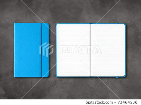 Blue closed and open lined notebooks on dark concrete background 73464530