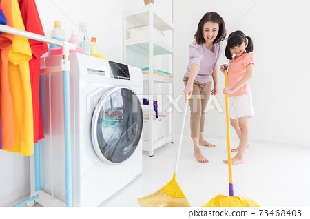 family mother and child girl cleaning floors in house with broom and mop 73468403