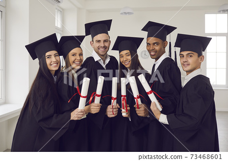 Group of happy multiethnic university graduates in black mantles standing with diplomas in hands 73468601