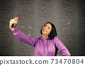Cheerful young brunette woman takes selfie using smartphone 73470804