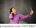 Cheerful young brunette woman takes selfie using smartphone 73470807