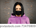 Serious young woman in black protective mask looking at you over home wall background 73470809
