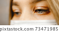 Macro eye view: Young female nurse with blue eyes wearing medical mask and looking down 73471985