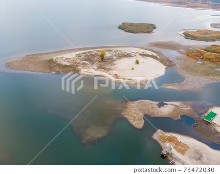 Scenic aerial drone birds eye view of swallow sand river or lake shore due to drought and water pond reservoir dam draining. Natural disaster of arid, warmand dry climate change 73472030