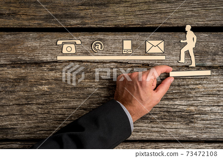 Assistance concept with a businessman supporting a cut out of a man climbing towards contact icons 73472108