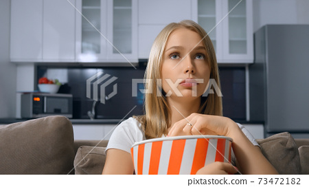 Blonde eating popcorn and watching TV. 73472182