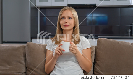 Blonde sitting with cup and watching TV. 73472184