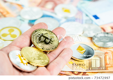 Silver and gold bitcoin coins on  palm and paper euro banknotes 73472997