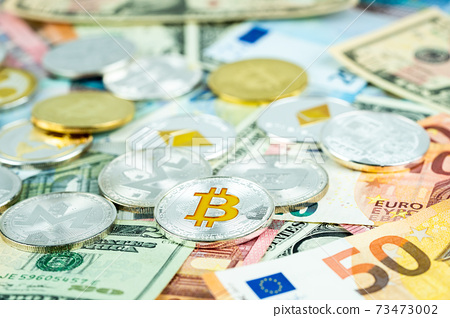 Various cryptocurrency coins on paper dollar and euro banknotes. Bitcoin, ethereum, litecoin and others modern virtual currency 73473002