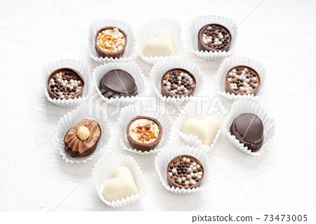 Different chocolate pralines. Belgian pralines of different shapes in paper baskets 73473005