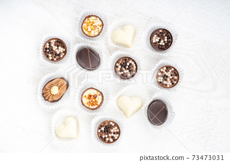 Different chocolate pralines. Belgian pralines of different shapes in paper baskets 73473031