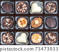 Different chocolate pralines. Box of belgian pralines of different shapes 73473033