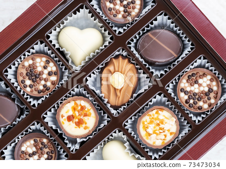 Different chocolate pralines. Box of belgian pralines of different shapes 73473034