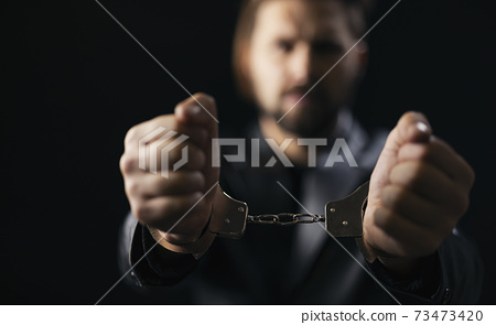 Man standing in handcuffs over black background 73473420