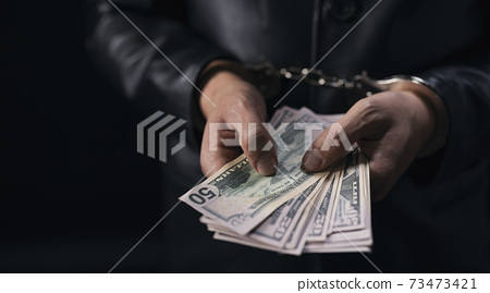 Man holding dollar banknotes with handcuffs on hands 73473421