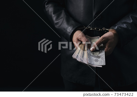 Close up of male hands in handcuffs holding money cash 73473422