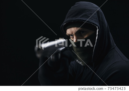 Angry gangster in mask holding weapon 73473423