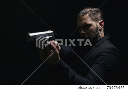 Real bandit aiming with gun over black background 73473425