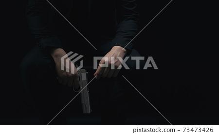 Gangster holding gun over black background 73473426