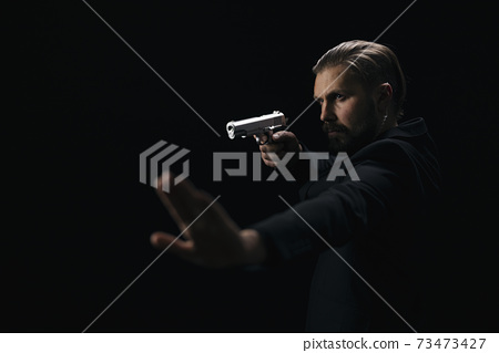 Man with gun showing sign stop with palm 73473427
