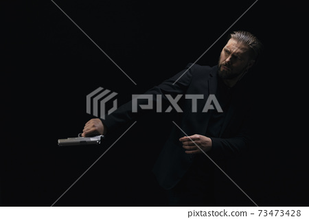 Brutal killer posing in studio with gun in hands 73473428