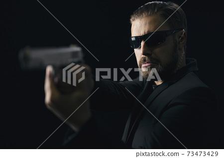 Bearded killer in sunglasses with gun in hands 73473429