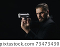 Serious man aiming with gun over black background 73473430