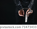 Gangster in handcuff holding real gun 73473433
