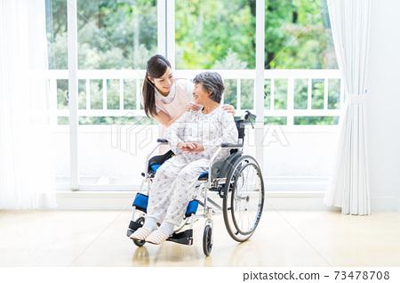 요양 시설에서 생활하는 노인 여성과 젊은 도우미 73478708