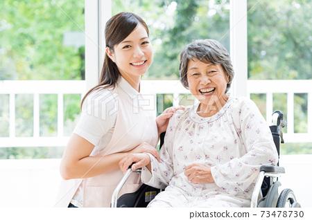요양 시설에서 생활하는 노인 여성과 젊은 도우미 73478730