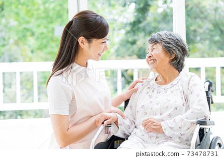 요양 시설에서 생활하는 노인 여성과 젊은 도우미 73478731