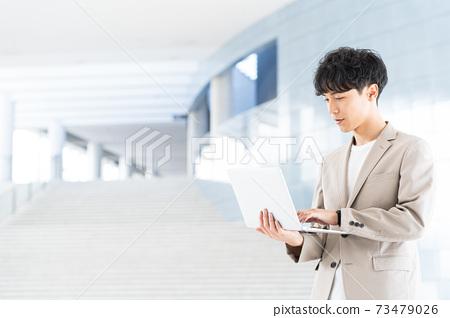 有一台膝上型計算機的年輕商人在辦公室 73479026