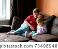 Mother and daughter at home use tablet pc. Motherhood, spending time with a child. Parental love. 73498948