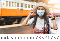 Asian women tourists at Bangkok train station. A female traveller wearing a mask while visiting a backpacker during the outbreak in new normal lifestyle with blur vintage train background, copy space. 73521757