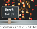 Do not Give up wrote on  blackboard over white wood table with colorful bokeh background 73524169