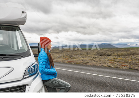 RV camper trailer travel woman driving motorhome camping van on Iceland road trip. Asian tourist driver taking break on adventure fall autumn vacation looking at nature landscape. 73528278
