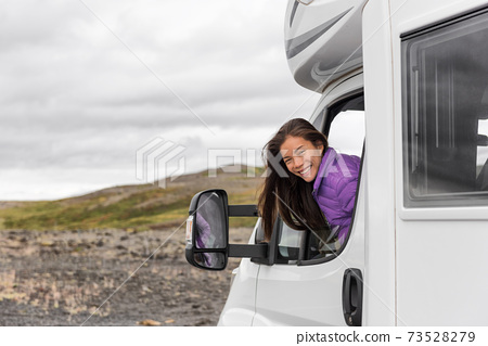 RV camper trailer travel woman driving motorhome camping van on Iceland road trip. Asian tourist driver smiling peeking out window of front seat 73528279