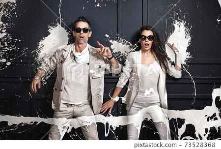 Portrait of an amazed couple covered with white paint 73528368
