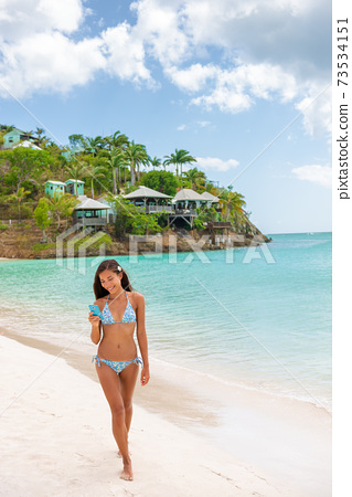 Beach selfie girl tourist walking on luxury resort vacation travel bikini woman having fun sharing photo online using social media app phone. Happy mixed race Caucasian Asian woman swimsuit model 73534151