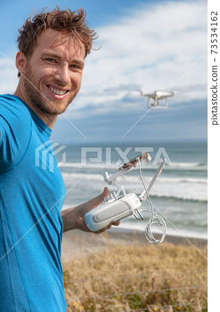 Person flying a drone on beach outdoors gaming young man pilot controlling drong with controller and smart phone taking selfie on travel vacation 73534162
