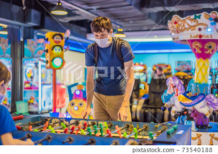 A young man wearing a medical mask during COVID-19 coronavirus playing table football indoors against a friend 73540188