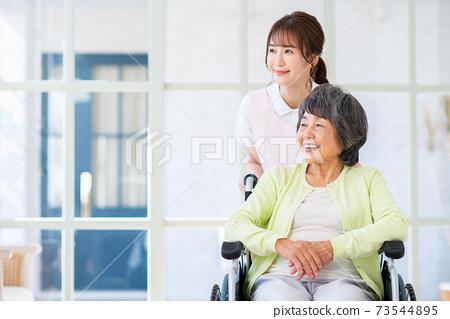 요양 시설 노인과 젊은 직원의 여성 73544895