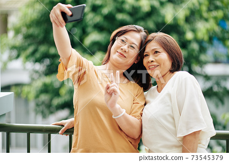 Senior women taking selfie 73545379