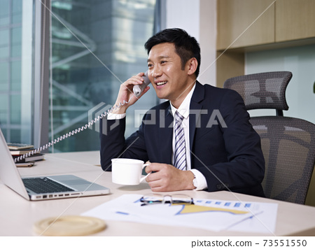 asian businessman talking on phone in office 73551550