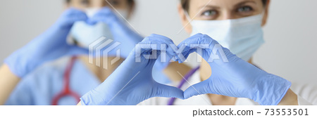 Two doctor in medical masks and rubber gloves showing heart with their hands 73553501