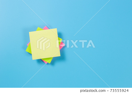 Stack empty sticky post note paper sheet on blue background. 73555924