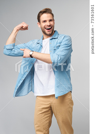 Portrait of a handsome man in jeans shirt showing his bicep with arm bended over grey background 73561601