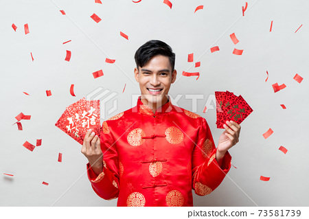 Asian man in traditional oriental costume holding red envelopes or Ang Pao 73581739